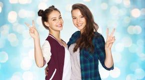 Adolescentes felices que abrazan y que muestran el signo de la paz Imagenes de archivo