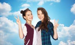 Adolescentes felices que abrazan y que muestran el signo de la paz Foto de archivo libre de regalías