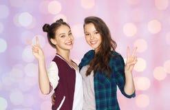 Adolescentes felices que abrazan y que muestran el signo de la paz Foto de archivo