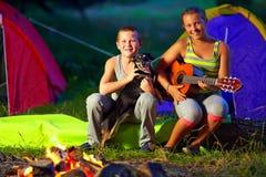 Adolescentes felices que cantan canciones alrededor del fuego del campo Foto de archivo libre de regalías