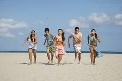 Adolescentes felices que corren en Sandy Beach Imágenes de archivo libres de regalías