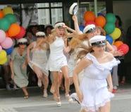 Adolescentes felices que corren hacia fuera de escuela después de la graduación Fotos de archivo