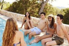 Adolescentes felices que cuelgan hacia fuera en el borde de una piscina Imagen de archivo