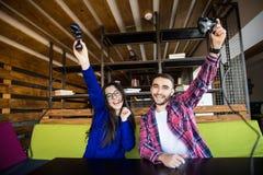Adolescentes felices que juegan al videojuego con el cojín del control en sala de estar Fotografía de archivo
