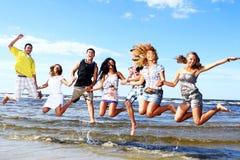 Adolescentes felices que juegan en el mar Imágenes de archivo libres de regalías