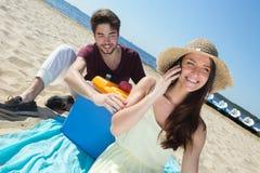 Adolescentes felices que llaman a sus amigos mientras que goza de la playa Foto de archivo