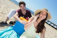 Adolescentes felices que llaman a sus amigos mientras que goza de la playa Fotos de archivo