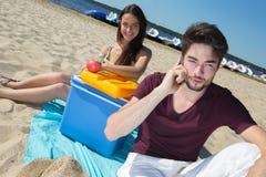 Adolescentes felices que llaman a sus amigos mientras que goza de la playa Imagen de archivo