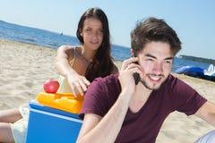 Adolescentes felices que llaman a sus amigos mientras que goza de la playa Foto de archivo libre de regalías
