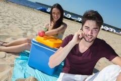 Adolescentes felices que llaman a sus amigos mientras que goza de la playa Imagenes de archivo