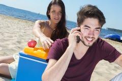 Adolescentes felices que llaman a sus amigos mientras que goza de la playa Fotografía de archivo