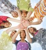 Adolescentes felices que llevan a cabo las manos juntas en la nieve Imagenes de archivo