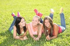 Adolescentes felices que mienten en la hierba Fotografía de archivo libre de regalías