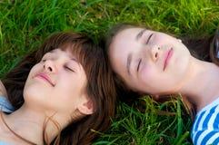 Adolescentes felices que mienten en la hierba Fotografía de archivo