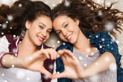 Adolescentes felices que mienten en piso con el corazón Imagen de archivo libre de regalías