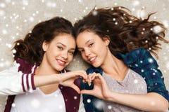 Adolescentes felices que mienten en piso con el corazón Foto de archivo libre de regalías