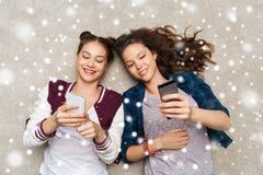 Adolescentes felices que mienten en piso con smartphone Foto de archivo libre de regalías