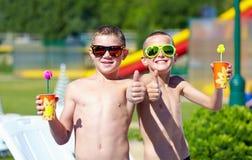 Adolescentes felices que muestran los pulgares para arriba en aquapark Foto de archivo libre de regalías