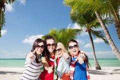 Adolescentes felices que muestran los pulgares para arriba en la playa Fotos de archivo