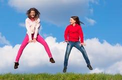 Adolescentes felices que saltan en el prado Fotografía de archivo