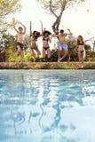 Adolescentes felices que saltan en una piscina al aire libre, vertical Foto de archivo