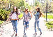 Adolescentes felices que se divierten en parque soleado del verano Tiempo caliente de la primavera Imagenes de archivo