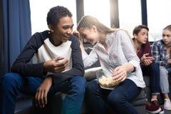 Adolescentes felices que se sientan en el sofá y que comen las palomitas del cuenco dentro Imagenes de archivo
