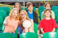 Adolescentes felices que se sientan en la tribuna durante juego Fotografía de archivo