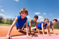 Adolescentes felices que sostienen el tablón al aire libre en la pista Fotografía de archivo libre de regalías