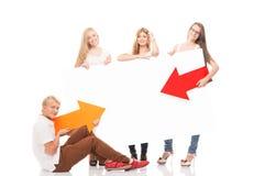 Adolescentes felices que sostienen indicadores y una bandera Foto de archivo