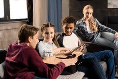 Adolescentes felices que tocan la guitarra acustic en casa Imagenes de archivo