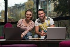 Adolescentes felices que usan el ordenador portátil en café Imagen de archivo