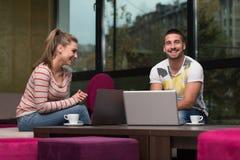Adolescentes felices que usan el ordenador portátil en café Foto de archivo