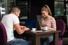 Adolescentes felices que usan el ordenador portátil en café Fotos de archivo