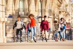 Adolescentes felices y muchachas rollerblading en ciudad Imagen de archivo libre de regalías