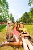 Adolescentes felices y perros agradables afuera en parque Fotografía de archivo libre de regalías