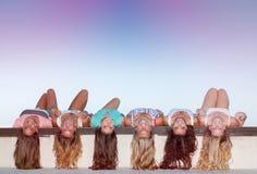 Adolescentes felizes com a colocação saudável longa do cabelo de cabeça para baixo Imagem de Stock