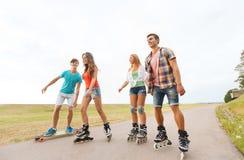 Adolescentes felizes com rollerblades e longboards Fotografia de Stock Royalty Free