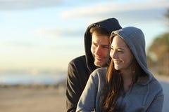 Adolescentes felizes que contemplam o por do sol na praia imagens de stock royalty free