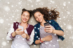 Adolescentes felizes que encontram-se no assoalho com smartphone Foto de Stock Royalty Free