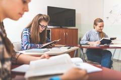 Adolescentes femeninos concentrados absorbedly que estudian Fotografía de archivo libre de regalías