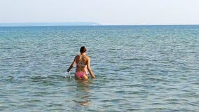 Adolescentes femeninos entran en la agua de mar Foto de archivo