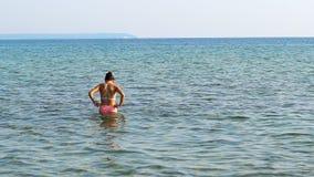 Adolescentes femeninos entran en la agua de mar Fotos de archivo