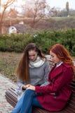 Adolescentes femeninos que discuten un libro que se sienta en el banco en un au Imagen de archivo libre de regalías