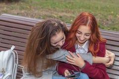 Adolescentes femeninos que escuchan la música en el smartphone que se sienta en el th Fotos de archivo libres de regalías