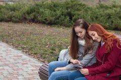 Adolescentes femeninos que escuchan la música en el smartphone que se sienta en el th Fotografía de archivo libre de regalías