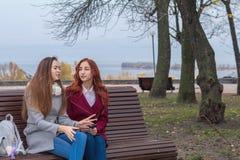 Adolescentes femeninos que escuchan la música en el smartphone que se sienta en el th Imágenes de archivo libres de regalías