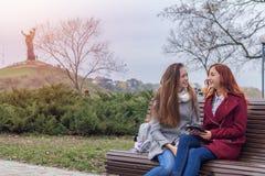 Adolescentes femeninos que escuchan la música en el smartphone que se sienta en el th Fotografía de archivo