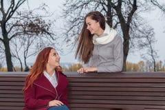 Adolescentes femeninos que escuchan la música en smartphone en el banco i Imagen de archivo