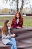Adolescentes femeninos que escuchan la música en smartphone en el banco i Imagenes de archivo